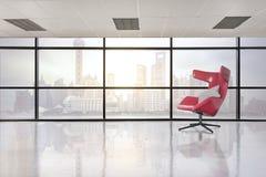 Modern röd stol i tomt kontorsutrymme med det stora fönstret arkivbild