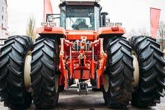 Modern röd traktor med stora hjul, hydraulisk hake, lyftande ram Arkivfoton