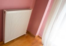 Modern radiator on color wall indoors. Central heating system stock photo