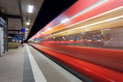 Modern railway station with high speed passenger train on railroad track in motion at night Stock Photos