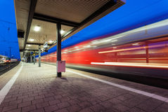 Modern railway station with high speed passenger train on railroad track in motion at night Royalty Free Stock Photo