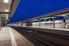 Modern railway station with high speed passenger train on railroad track in motion. Railway platform at night  in Nuremberg Royalty Free Stock Photos