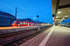 Modern railway station with passenger train on railroad track at night  in Nuremberg, Germany. Fast red commuter train Stock Photo