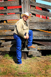 Modern Rancher. A typical modern unshaven rancher stands by an old weathered loading chute. Red barn in background stock images