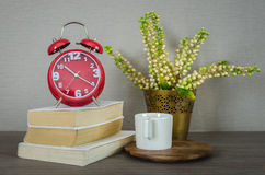 Modern red alarm clock on book with cup on wood tray Stock Photography