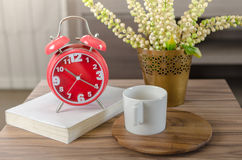 Modern red alarm clock on book with cup on wood tray Royalty Free Stock Image