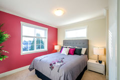 Modern red bedroom. Modern bedroom interior with a red wall, designer pillows, and a floral duvet cover in a luxury house Stock Photography