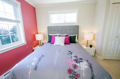 Modern red bedroom. Modern bedroom interior with a red wall, designer pillows, and a floral duvet cover in a luxury house Stock Photos
