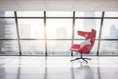 Modern red chair in empty office space with large window Stock Image