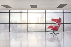 Modern red chair in empty office space with large window Stock Photography