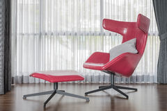 Modern red chair on wooden floor with curtain Royalty Free Stock Photo