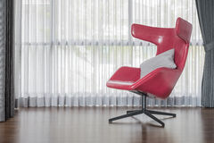 Modern red chair on wooden floor with curtain Royalty Free Stock Photos
