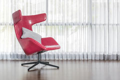 Modern red chair on wooden floor with curtain Stock Photos