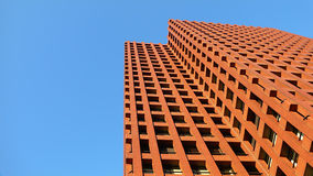 Modern red color upstairs building. And bright blue sky background Royalty Free Stock Images