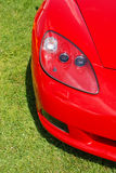 Modern red corvette. On green meadow Stock Photos