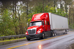 Modern red glossy in rain semi truck trailer on raining road