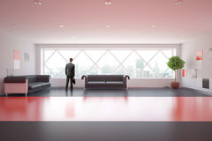 Modern red interior with sofas. Man standing in modern red business interior with comfortable sofas, decorative plant, ceiling lamps and city view. 3D Rendering Stock Image