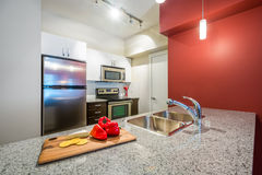 Modern red kitchen. Modern clean red kitchen with stainless steel appliances and a cutting board with cheese, crackers, and red peppers. Interior design Stock Images