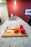 Modern red kitchen. Interior with a cutting board with cheese, crackers, and red peppers Royalty Free Stock Photo