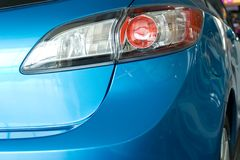 Modern red rear light of a blue car. Rear of modern blue car with closeup on a red rear light Stock Photos