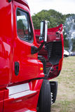 Modern red semi truck with open hood on parking lot Stock Photo