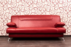 Modern red sofa in front of the wall Royalty Free Stock Images