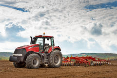 Modern red tractor. Modern red tractor in the agricultural field stock photos