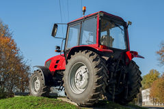 Modern red tractor on a blue sky background. Modern bright red tractor outdoors Stock Photos