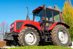 Modern red tractor on a blue sky background Stock Photography
