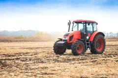 Modern red tractor in the field. Modern red tractor in the field on a bright sunny day Stock Photo