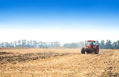 Modern red tractor in the field. Modern red tractor in the field on a bright sunny day Stock Photography