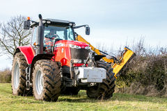 Modern red tractor hedge cutting Royalty Free Stock Photography