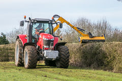 Modern red tractor hedge cutting. Modern red massey Ferguson tractor cutting trimming tidying and maintaining hedge in field Stock Images