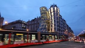 Modern red tram is passing Dancing House in Prague stock video