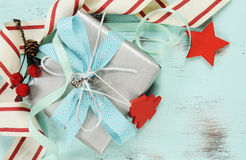 Modern red and white Christmas decorations on aqua blue wood background, with silver gift closeup. Royalty Free Stock Images