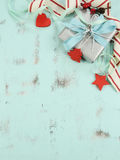 Modern red and white Christmas decorations on aqua blue wood background, with silver gift - vertical. Stock Image