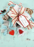 Modern red and white Christmas decorations on aqua blue wood background, with white gift closeup - vertical. royalty free stock photography