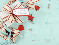 Modern red and white Christmas decorations on aqua blue wood background, with white gift and copy space. Royalty Free Stock Images