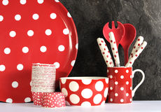 Modern Red and White Polka Dot Kitchen. With large platter plate, cupcake pans, bowl, coffee mug, cutlery and serving spoons against black slate and white Royalty Free Stock Image