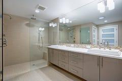 Modern refreshing bathroom with a beige dual washstand. Modern refreshing bathroom features a beige dual washstand accented with mosaic backsplash beneath a stock photos