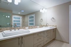 Modern refreshing bathroom with a beige dual washstand. Modern refreshing bathroom features a beige dual washstand accented with mosaic backsplash beneath a royalty free stock image