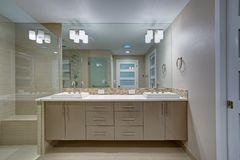 Modern refreshing bathroom with a beige dual washstand. Modern refreshing bathroom features a beige dual washstand accented with mosaic backsplash beneath a royalty free stock photo