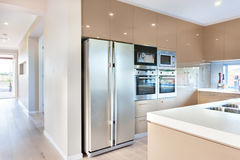 Modern refrigerator in the luxury kitchen with microwave ovens. Expensive and modern kitchenware including silver color and tall two door refrigerator and four Stock Photos