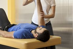 Modern rehabilitation practice. Young female physiotherapist training with colleague. Practice hand therapy . Close up Stock Image