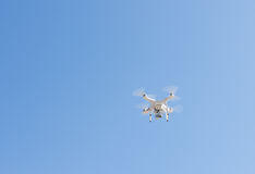 Modern Remote Control Air Drone Flying with action camera. White drone, quadrocopter, with photo camera flying in the blue sky Royalty Free Stock Images