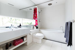 Modern renovated white mosaic tiled family bathroom with red and Royalty Free Stock Photos
