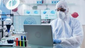 In modern research facility chemist in coverall is working on laptop. Modern equipments and tubes with various colored liquids are present stock footage