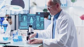 In modern research facility mature chemist is taking notes. After studying a sample using the microscope stock video
