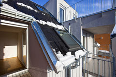 Modern residential building. Roof top of a modern residential building with skylight and opened terrace door - some melting snow symbolise climate, alternative royalty free stock photos