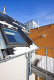 Modern residential building. Roof top of a modern residential building with skylight and chimney - some melting snow symbolise climate, alternative energy royalty free stock photos